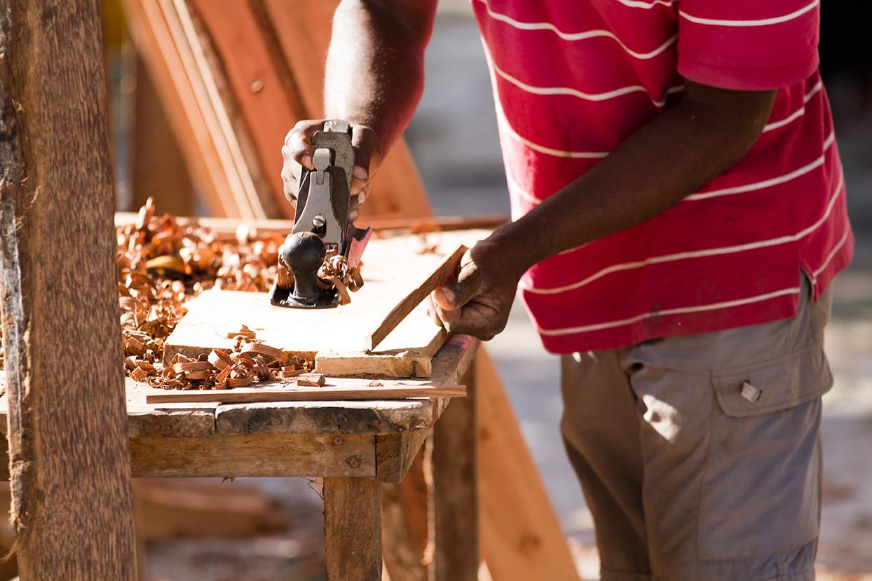 Un menuisier rabote une planche de bois en Afrique