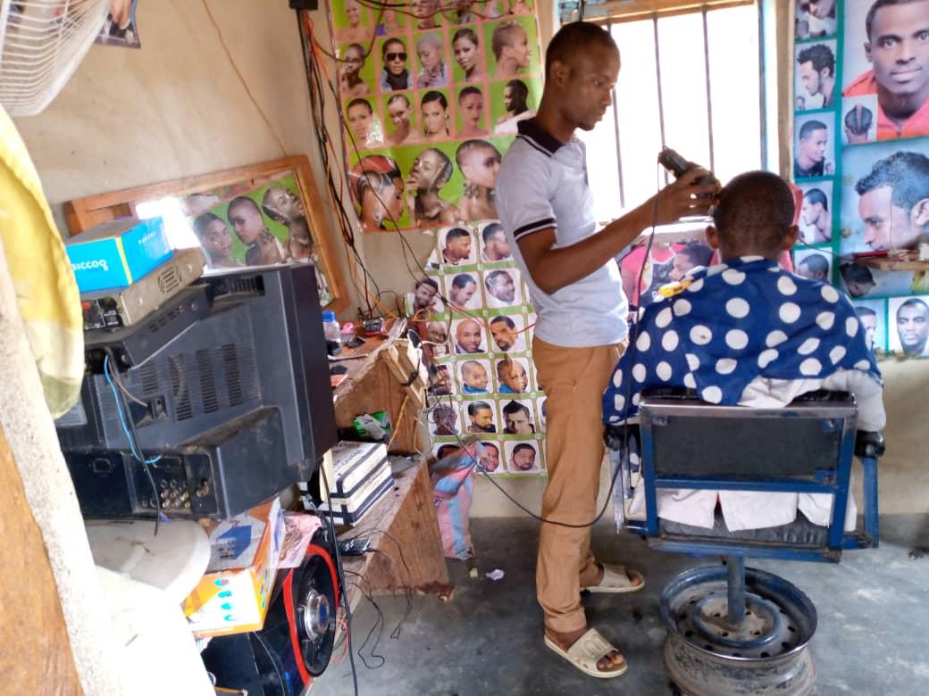 Salon de coiffure électrifié, avec une tondeuse électrique, une télévision, un ventilateur et une sono.