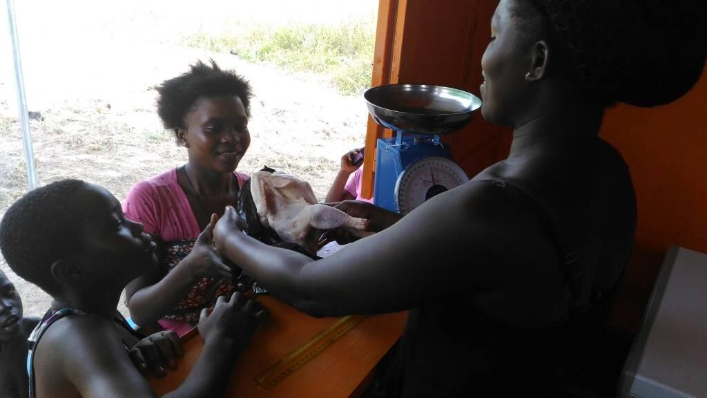 Une femme entrepreneure vend un poulet à une cliente en Afrique