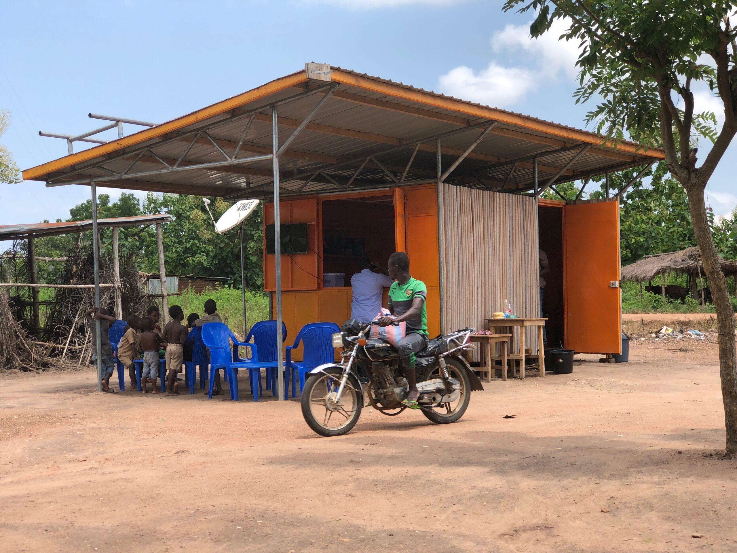 Une moto passe devant un kiosque solaire Benoo Energies dans un village au Togo en Afrique