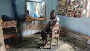 Jeune homme assis près d'un ventilateur dans un salon de coiffure à Atchanvé au Togo