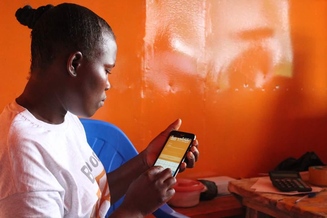 Une femme entrepreneure consulte son application de gestion sur son téléphone portable dans un kiosque solaire