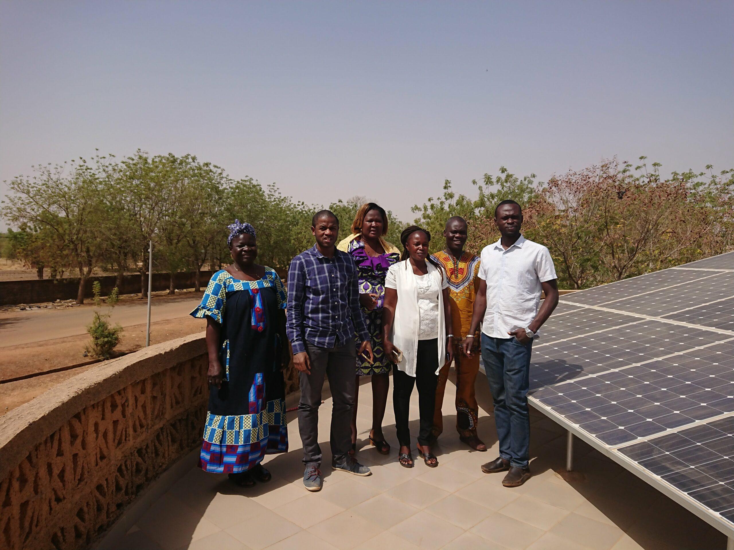 Bubacar Diallo de Benoo avec 5 membres d'A2N, posant devant des panneaux solaires au Burkina Faso.