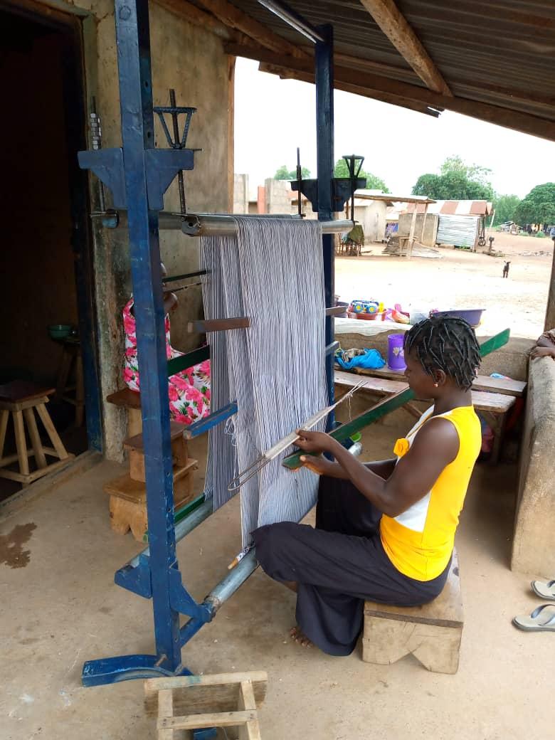 Une femme tisse sur un métier à tisser en Afrique