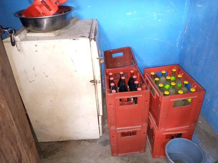 Un petit réfrigérateur à côté de caisses de sodas dans un maquis en Afrique